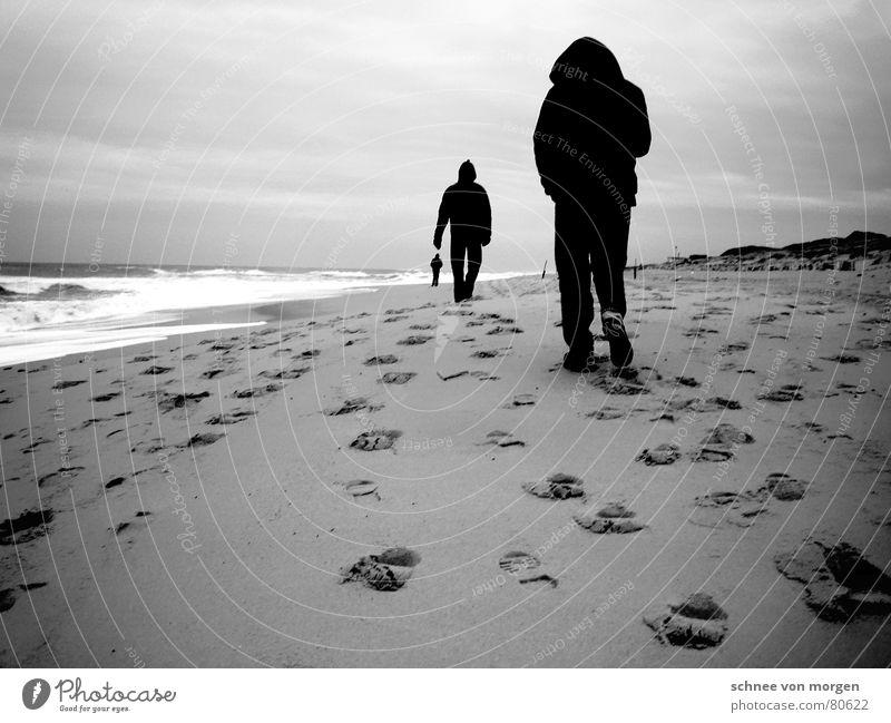 Perspektivwechsel Strand Meer See Fußspur schwarz weiß grau 3 Mann Wellen Wind Sturm Leidenschaft Kapuze Schwarzweißfoto Winter Wasser Spuren Beine Stranddüne