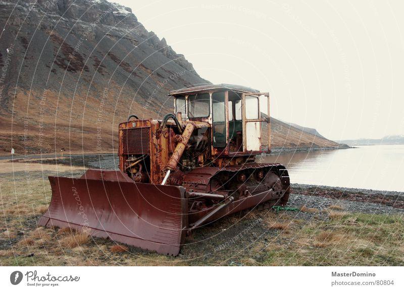 bulldoze the fjord away Planierraupe See Außenaufnahme Westfjord Baustelle vergangen Luft Bauarbeiter Rost Maschine kaputt Island Meer Gras Elektrisches Gerät