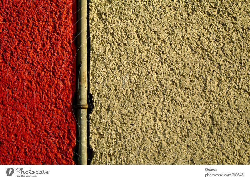 Regenrohr Wand Gebäude Putz Fallrohr Stahl rot beige Bauwerk Mauer Steigrohr Detailaufnahme rohrschelle entwässerung. balkonentwässerung dachentwässerung
