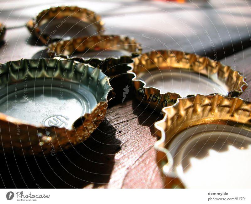 goldene Kronkorken Holz Tisch Abenddämmerung Flaschenverschluss