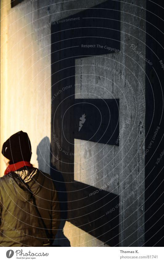 EI Spaziergang Mauer Wand Beton Buchstaben Kapuze Mütze Schal Licht Jacke Abendsonne Sonnenuntergang Lichteinfall Mensch gehen Mantel Kopfbedeckung Gürtel