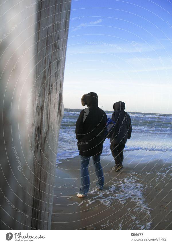 Frostiges Wetter Mensch Mann Himmel Meer blau Strand Holz Sand Wellen Küste Jacke Kapuze Schaum