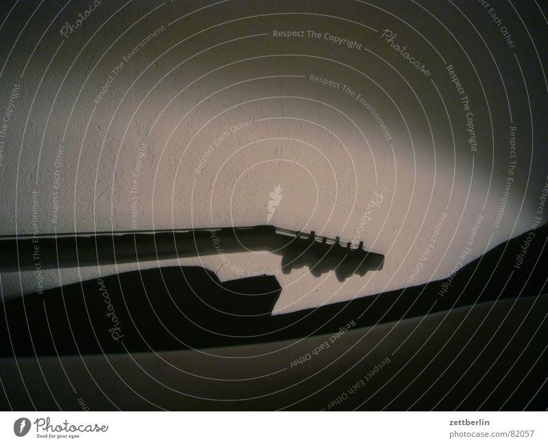 Gitarre zur Nacht (2) Luftkissenboot Bett Liege Pritsche Lampe Wand Putz Kissen schlafen Mauer Einsamkeit ruhen Schatten Schattendasein Ruhemöbel Sofa Trauer