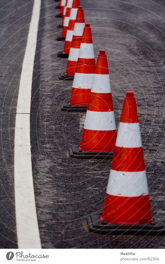 Hütchen weiß rot schwarz Straße dunkel Regen Linie nass Schilder & Markierungen Verkehr gefährlich Sicherheit Streifen Pause Wandel & Veränderung Asphalt