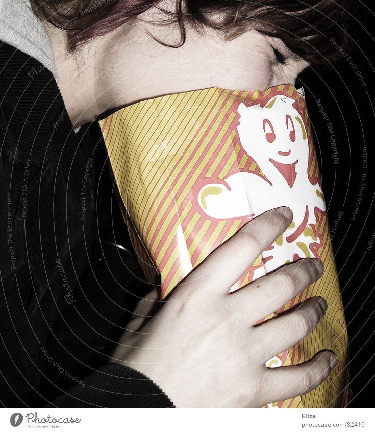 Eine Frau im Kino die ihr Gesicht in eine Popcorntüte hält frau popcorn lustig Popkorn Film schlecht übergeben Mensch Übelkeit Quatsch Kritik Gefühle