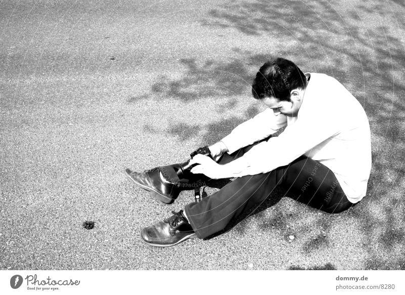 Der Fotograf Mensch Mann weiß Sonne schwarz sitzen Bodenbelag Fotokamera Schönes Wetter Stativ Tannenzapfen