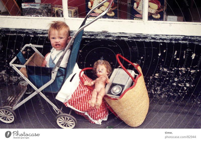 Exile on Main Street Blick Kind Kleinkind Mädchen Arme Kleinstadt Verkehrsmittel Straße Kinderwagen Tasche blond Spielzeug Puppe fahren Traurigkeit warten