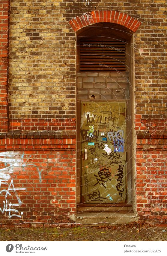 Wand mit Tür Sachbeschädigung Terrakotta Gebäude Mauer Backstein rot Gitter Eingang Zugang verfallen Patina Schmiererei Fenstersims Glasbaustein Binderstein