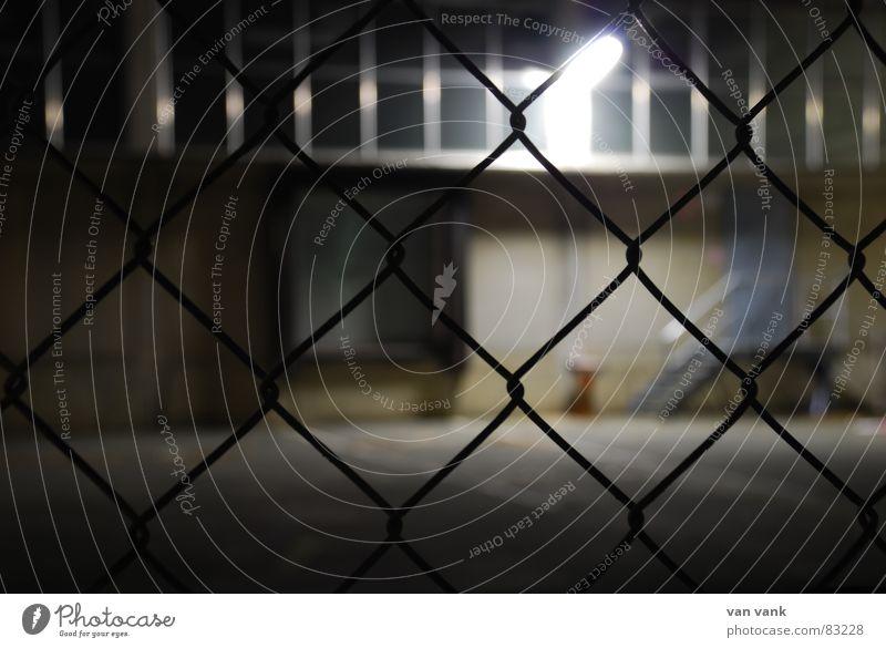 vernetzt Gitter Zaun geschlossen Licht Lampe Belichtung Asphalt Draht Maschendraht Fenster Nacht dunkel kalt Aschenbecher Einsamkeit Trauer Wand Mauer Fabrik