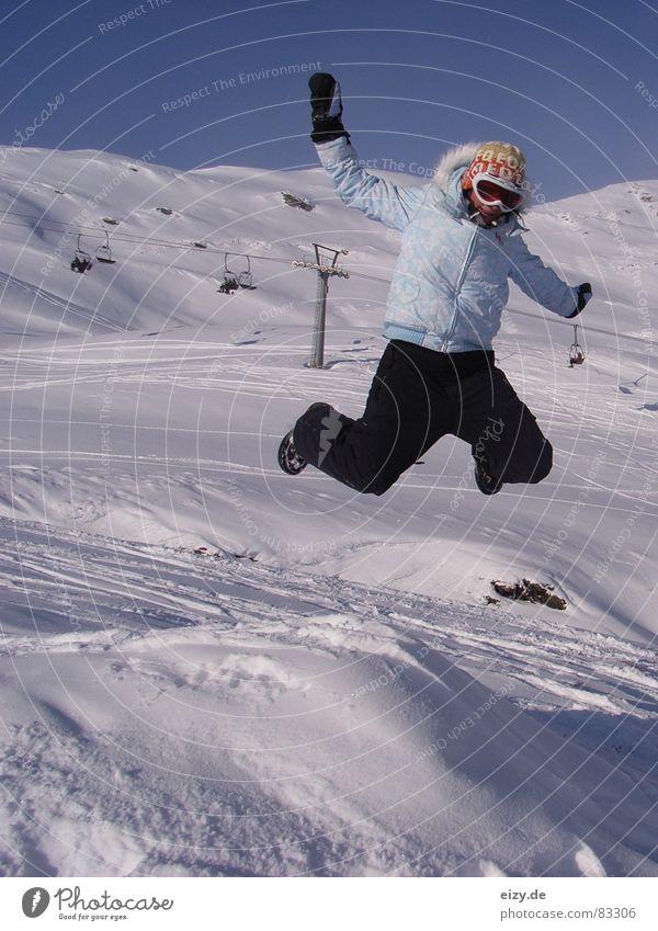 jump Frau Stil Österreich Freude Wintersport Berge u. Gebirge Schnee Skipiste genießen springen Schneebrille Witz Körperhaltung Skilift Sesselbahn hoch