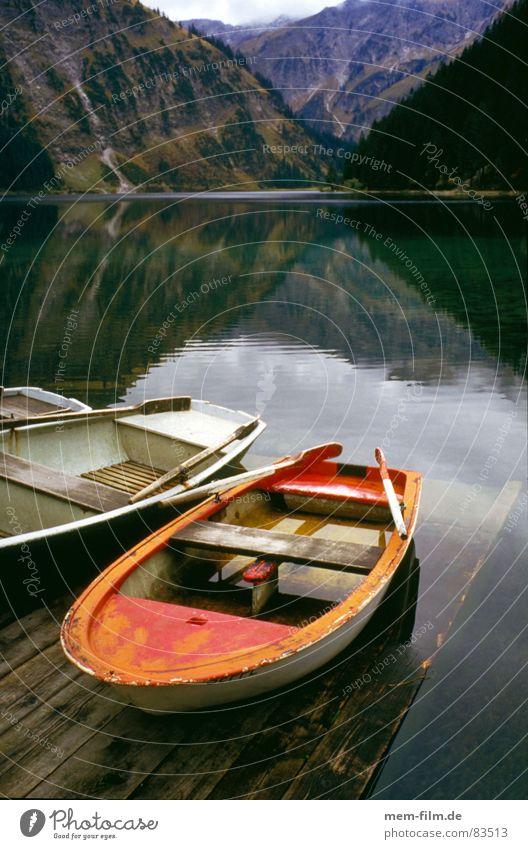 bergsee See Ruderboot Gebirgssee rot Wasserfahrzeug Erholung Berge u. Gebirge Schifffahrt klares wasser Alpen Natur Kontrast postkartenmotiv