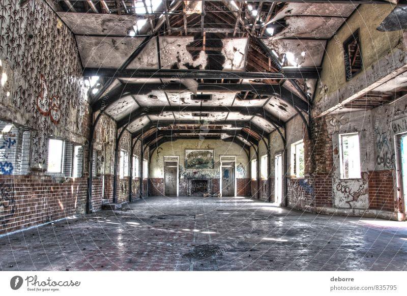 Blick auf den großen Saal in einem heruntergekommenen Gebäude mit Graffiti und zerbrochenen Fenstern. Menschenleer Haus Ruine Bauwerk Stein Beton Holz alt Armut