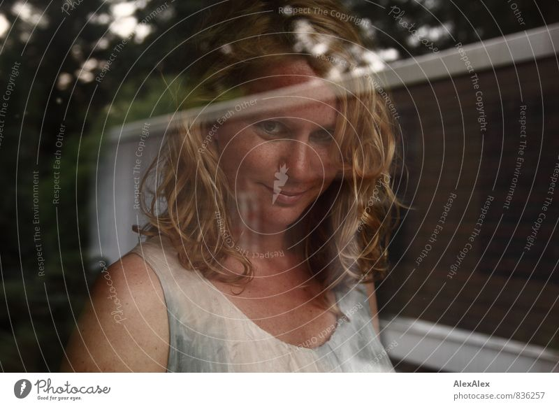 Schaufenster Junge Frau Jugendliche Sommersprossen Grübchen 30-45 Jahre Erwachsene Haus Garten Kleid blond langhaarig Locken Glas beobachten Lächeln ästhetisch