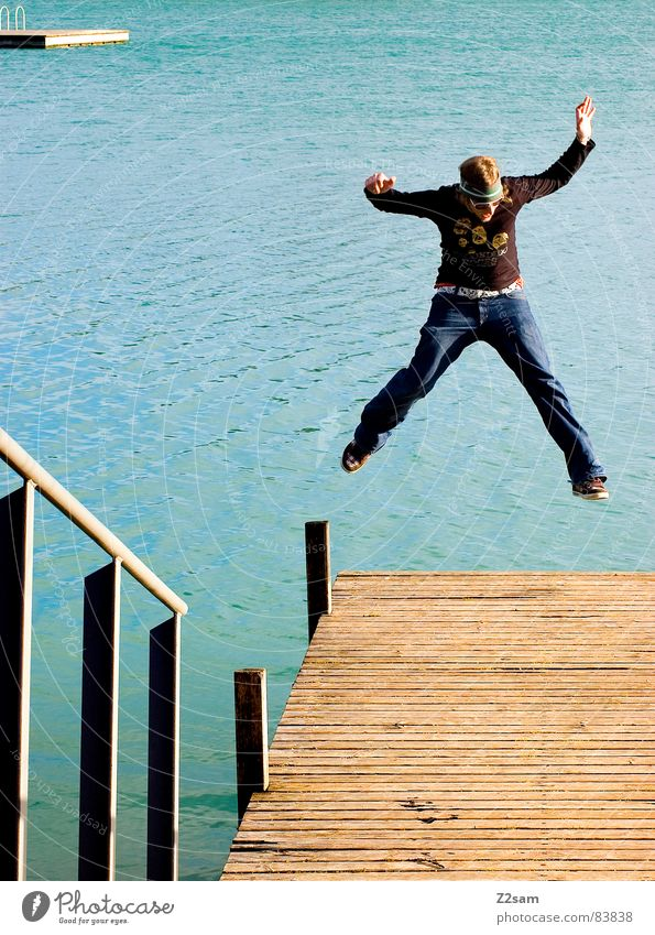 freudensprung Mensch Mann Wasser Freude gelb springen Stil Bewegung Holz See Wärme Beine Aktion Jeanshose Insel kaputt