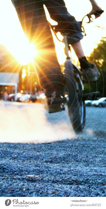 Bremsung Staub dreckig fahren Parkplatz Rad Fahrrad Gegenlicht Kieselsteine Abend Sonnenuntergang Jeanshose Streusand Freude Funsport Sport Spielen pegs BMX