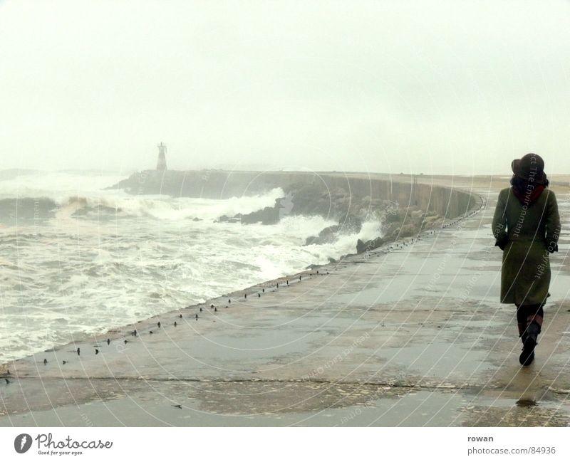 Spaziergang am Meer I überschwemmt See Frau Wellen Leuchtturm Gischt Nebel Pfütze Mantel grün gehen Bewegung unruhig Sturm nass kalt grau Wolken leer Wind