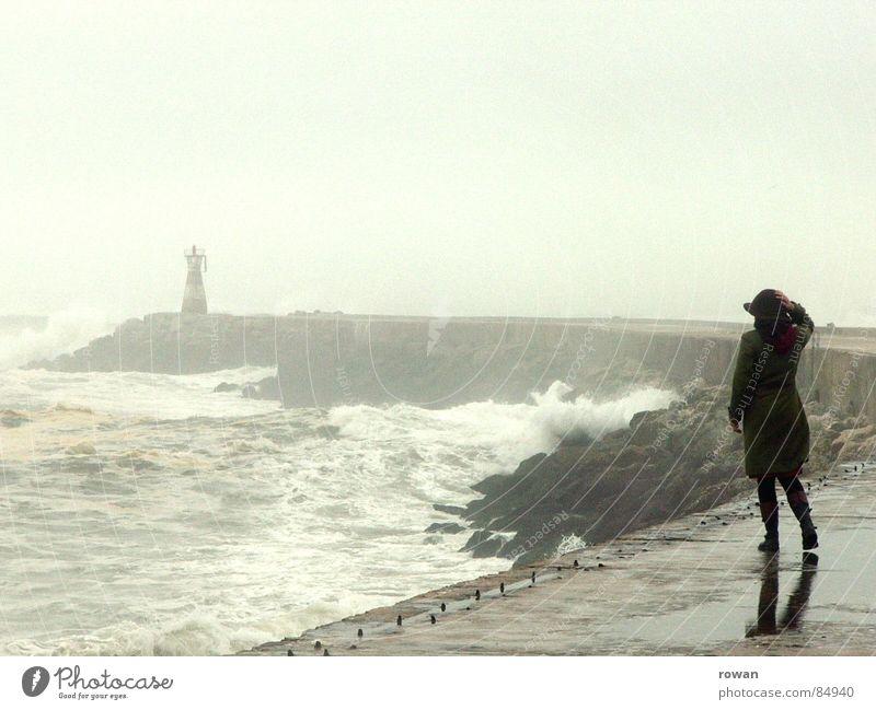 Spaziergang am Meer II überschwemmt See Frau Wellen Leuchtturm Gischt Nebel Pfütze Mantel grün gehen Bewegung unruhig Sturm nass kalt grau Wolken leer Wind
