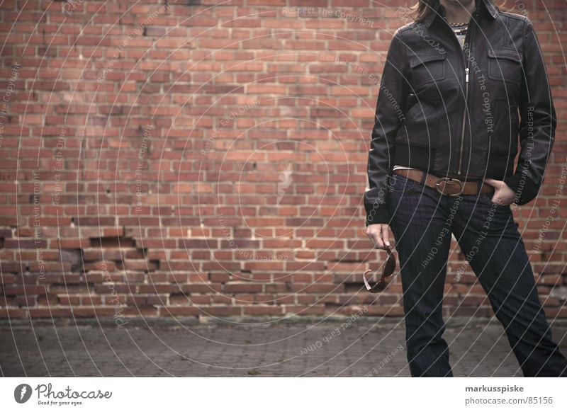 nur nicht zu cool Frau Stil Bekleidung Jeanshose Körperhaltung Backstein Sonnenbrille Hinterhof Gürtel Lederjacke