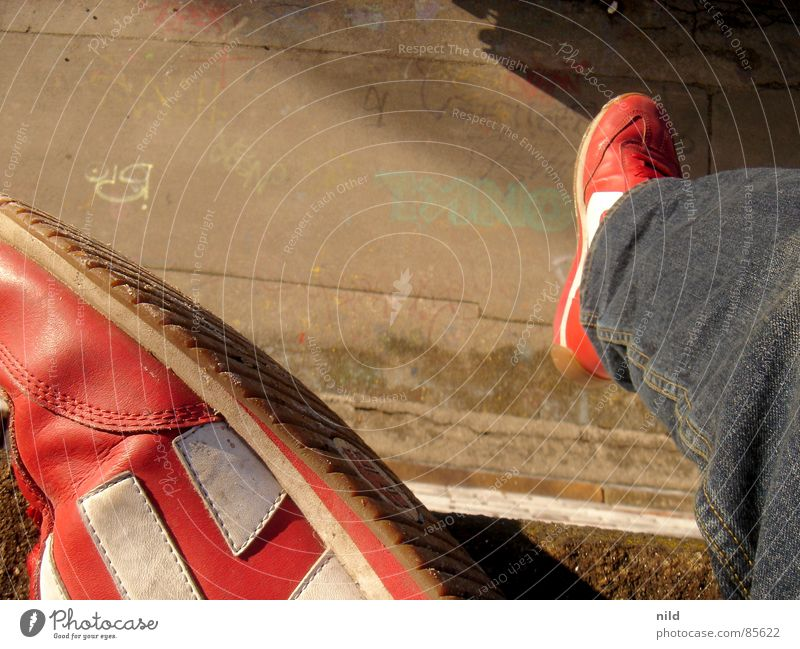 füsse lassen baumeln Etnies Schuhe Silhouette Asphalt Vogelperspektive Graffiti hängen lassen Schweben Verkehrswege Wandmalereien München Graffities Jeanshose