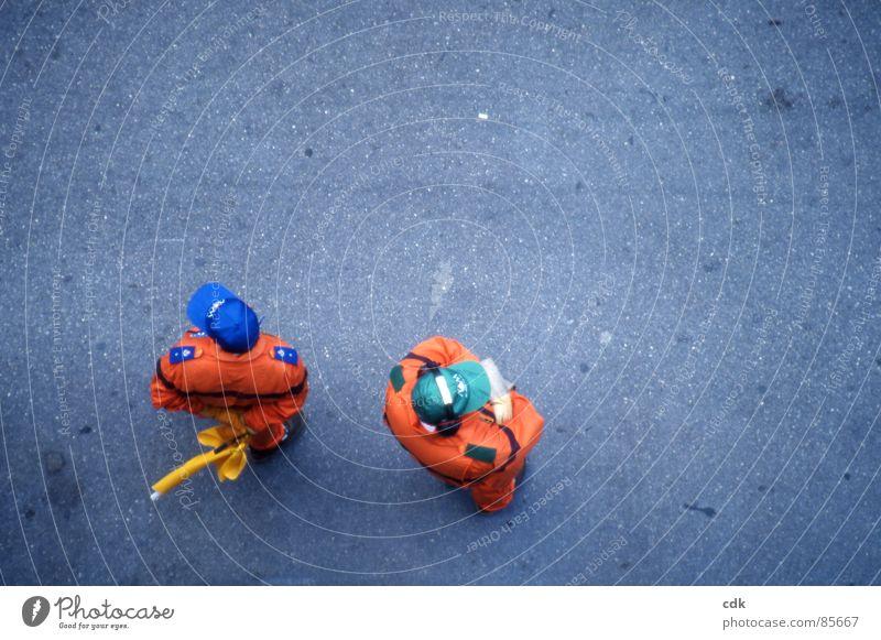 Wie sieht's aus? Mensch Mann Erholung ruhig Straße Wege & Pfade grau Denken Paar 2 Arbeit & Erwerbstätigkeit Zusammensein orange warten stehen mehrere