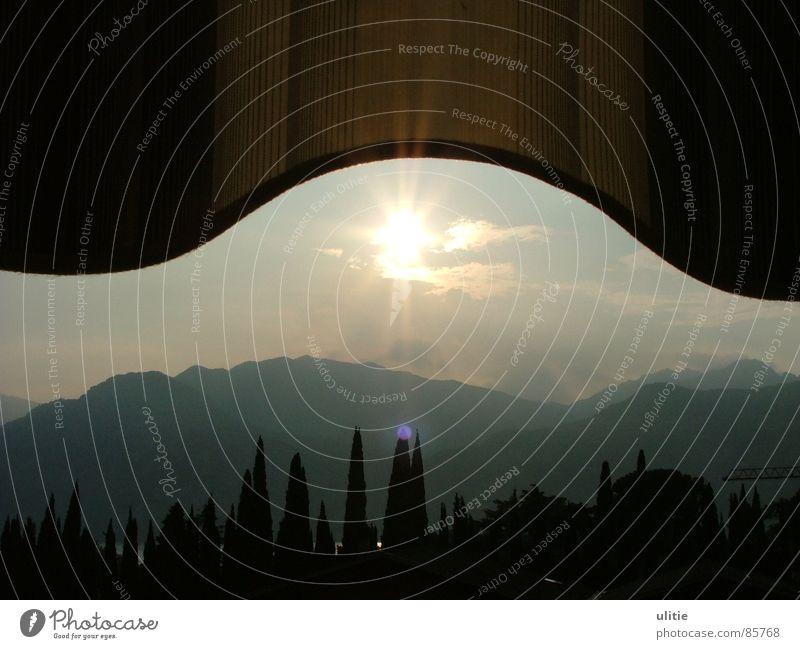 Wellen Himmel Sonne Sommer schwarz Berge u. Gebirge grau glänzend rund Spitze Abenddämmerung Abendsonne Markise Schutzdach Pinie Gardasee