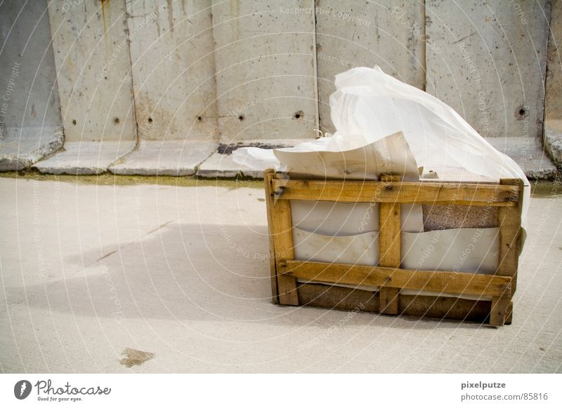 -> verweht <- Holzkiste Schatztruhe aufräumen grau Wand Mauer Schattenspiel Wind Sandverwehung Sturm Abdeckung Folie massiv Stabilität kaputt gelb Orkan nass