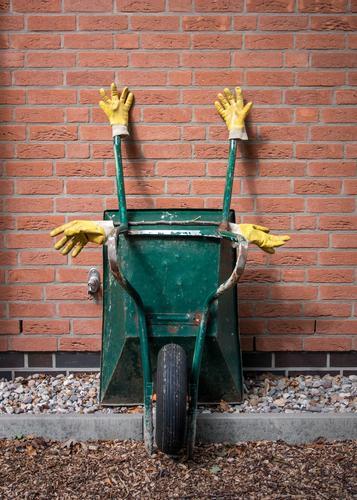 kreuzweise   feierabend! grün gelb Wand Mauer genießen schlafen Zeichen Backstein hängen Skulptur Gartenarbeit Feierabend Handschuhe gekreuzt Backsteinwand