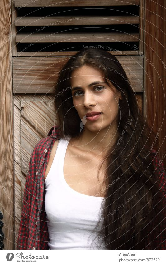 aussenwerbung Junge Frau Jugendliche Gesicht 18-30 Jahre Erwachsene Hemd Unterhemd schwarzhaarig langhaarig Holztür beobachten Kommunizieren Lächeln ästhetisch