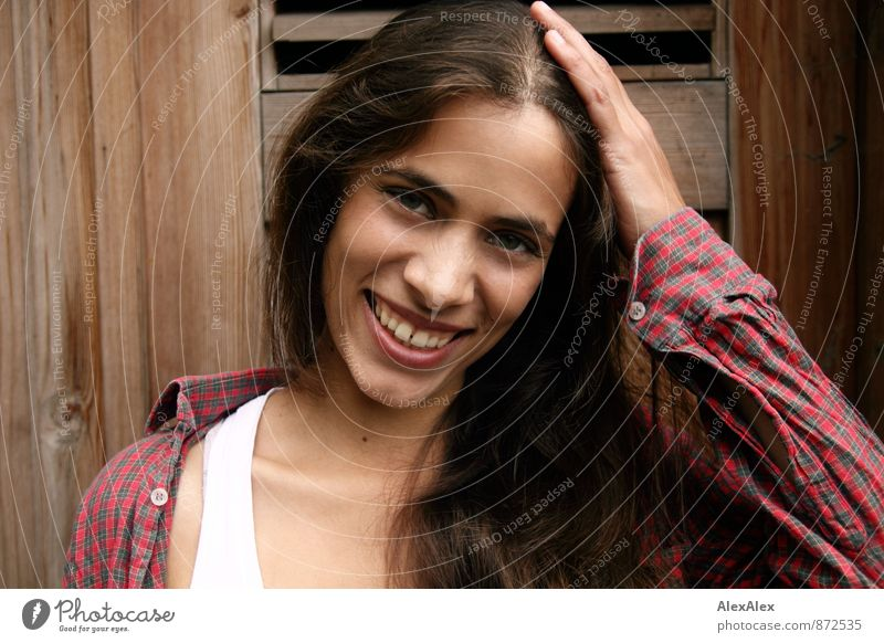 Portrait einer jungen, schönen, lachenden Frau vor einer Holztür Junge Frau Jugendliche 18-30 Jahre Erwachsene Hemd Unterhemd brünett langhaarig Kommunizieren