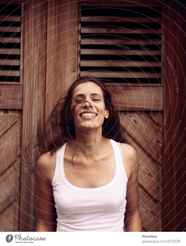Junge Frau vor einer Holztür schwenkt lachend ihr langes Haar Jugendliche 18-30 Jahre Erwachsene Unterhemd schwarzhaarig langhaarig Bewegung Lächeln ästhetisch