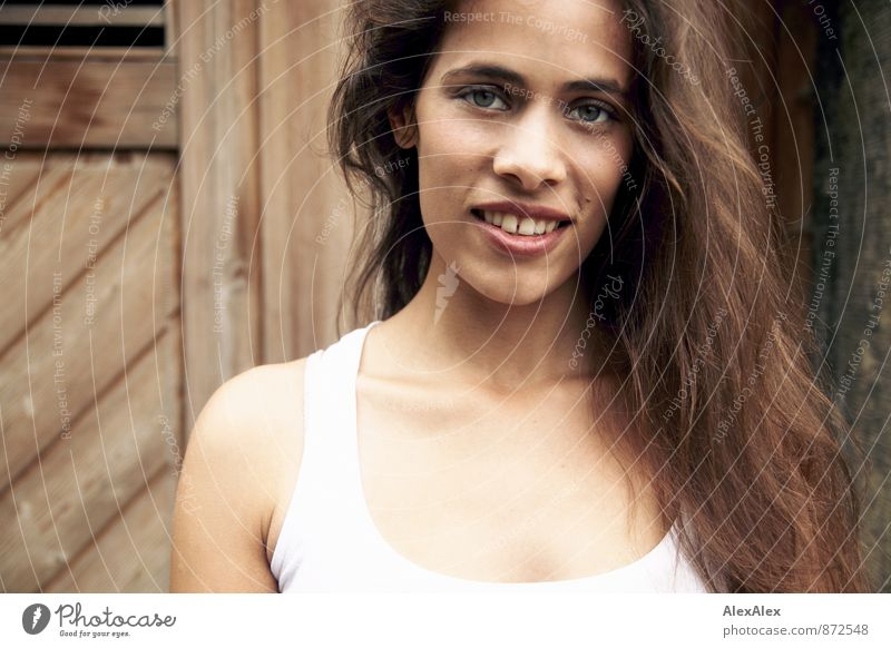 Portrait einer schönen, jungen, lächelnden Frau vor einer Holztür Junge Frau Jugendliche Gesicht 18-30 Jahre Erwachsene Unterhemd schwarzhaarig langhaarig