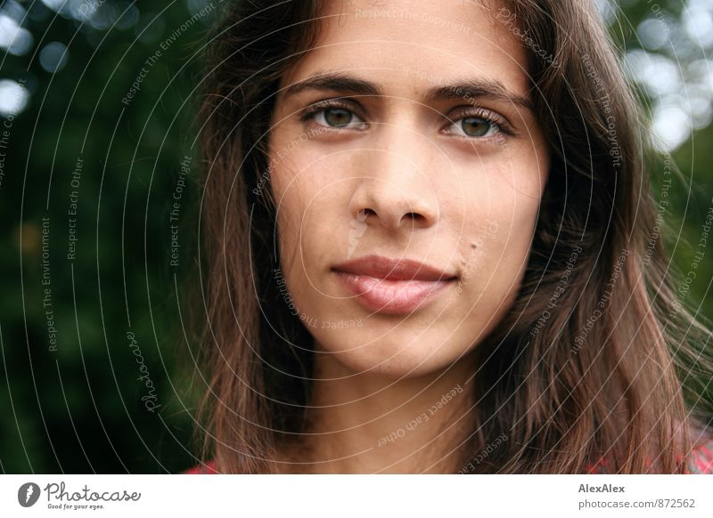 Portrait einer jungen, schönen Frau vor einem Baum Junge Frau Jugendliche Gesicht Auge 18-30 Jahre Erwachsene Park grünäugig schwarzhaarig langhaarig beobachten