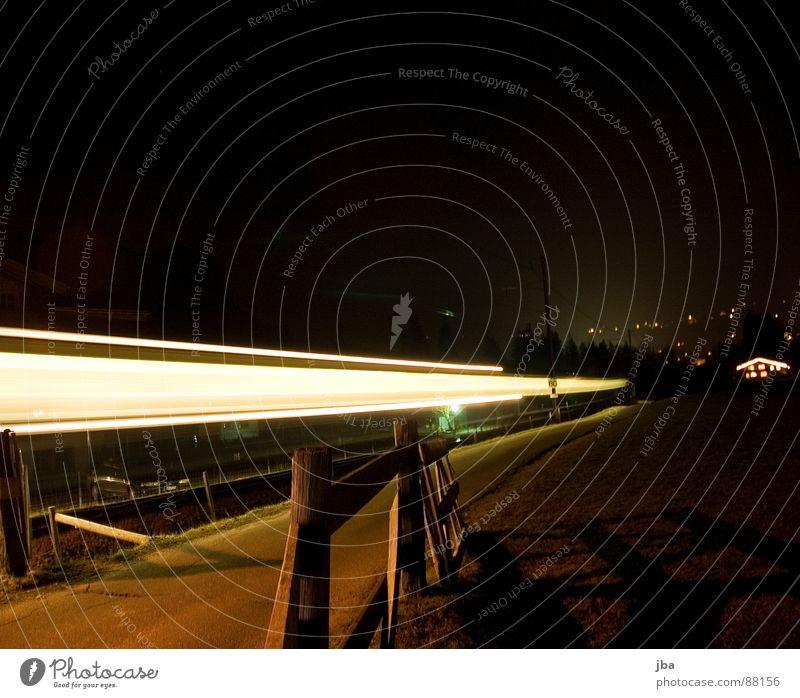 Der Zug schwarz Holz Beleuchtung Verkehr Eisenbahn fahren Dorf Gleise Zaun erleuchten Scheinwerfer Teer gestellt Holzpfahl