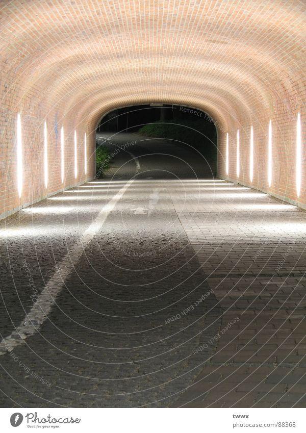 Weg wohin ? Einsamkeit Verkehr leer Ziel Unendlichkeit Tunnel Backstein Richtung Bürgersteig Kopfsteinpflaster verloren Straßenbeleuchtung Neonlicht anonym Straßenbelag