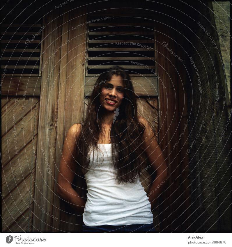 analoges Portrait einer jungen, langhaarigen, schönen Frau vor einer Holztür Junge Frau Jugendliche 18-30 Jahre Erwachsene Mauer Unterhemd brünett Lächeln