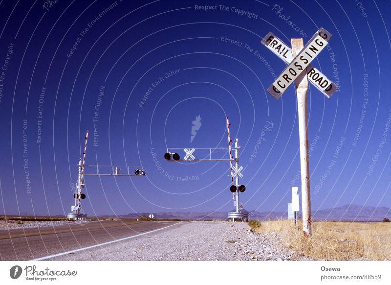 irgendwo in Arizona Steppe Schranke Gleise weiß Asphalt Gras trocken Ampel Bahnübergang Eisenbahn Verkehr Straßennamenschild USA Wüste Bahnschranke Himmel blau