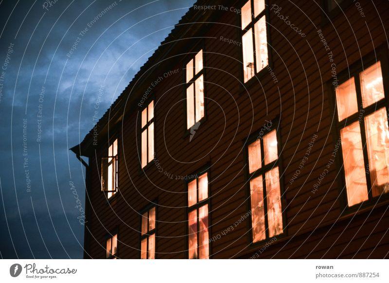nachts Haus Einfamilienhaus Fenster dunkel leuchten Holzhaus heimelig Häusliches Leben Wohnung Geborgenheit Wärme Schutz Farbfoto Außenaufnahme Menschenleer
