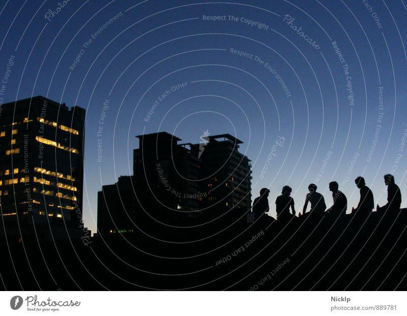 sechs junge Menschen sitzen im Gegenlicht der Abenddämmerung vor der Silhouette einer Großstadt (Melbourne) Sonnenuntergang Freiheit Freude Sommer Freundschaft