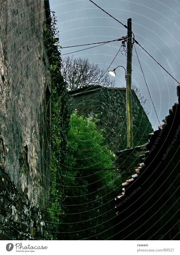 Dämmerung Dorf Laterne Licht dunkel Nacht Mauer Haus halbdunkel Wolken schlechtes Wetter Elektrizität Strommast Einsamkeit leer trist Efeu Vergangenheit Verfall