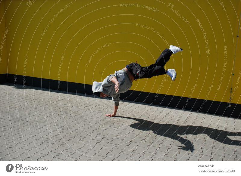händelbar gelb Lokal Asphalt Wand Parkplatz Sommer Schattenspiel Sport Spielen break Breakdancer Kapuze Tanzen