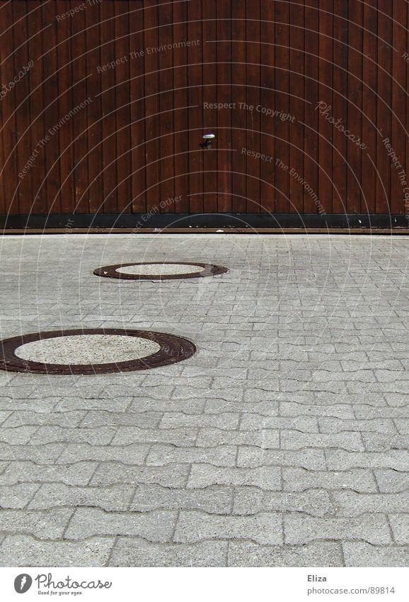 Gulligehabe Garagentor Einfahrt Fahrzeug Abstellplatz Holz Stein Gully Abfluss Kanalisation Kreis braun grau rund Geometrie Holzbrett bewachen Gegenteil