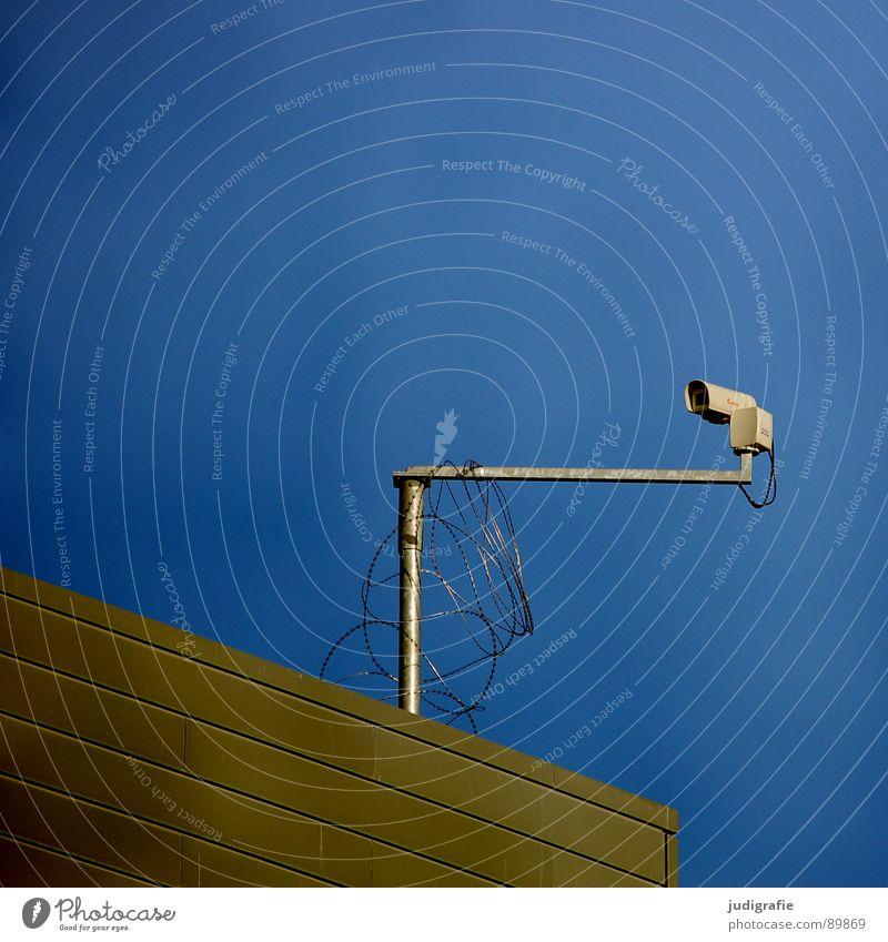 Auge Überwachungskamera beobachten Sicherheit Haus Gebäude Dach Stacheldraht Verkehrswege Detailaufnahme Fotokamera Überwachungsstaat Schutz Himmel blau