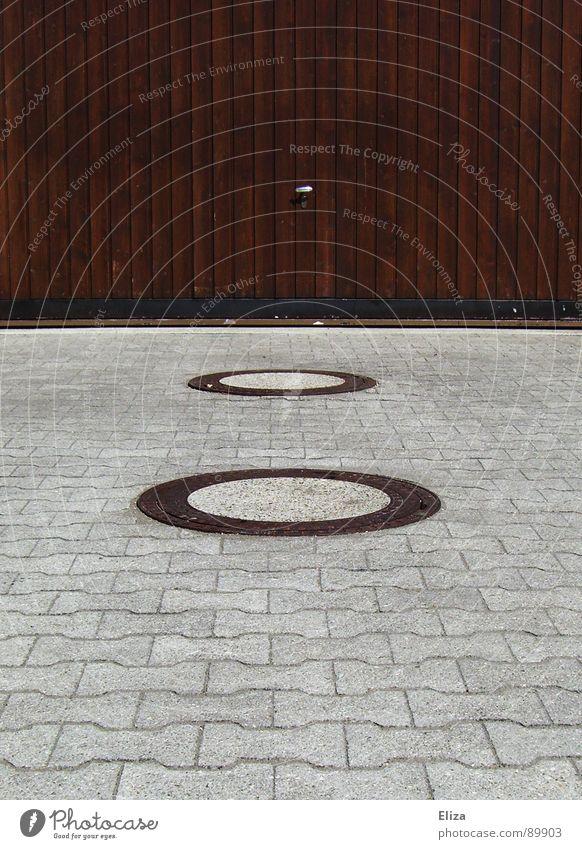 Gulligehabe, aber nur fast zentriert. Auge Regen Verkehrswege Fahrzeug Stein Holz Linie rund braun grau Garagentor 2 Einfahrt Abstellplatz Gully Abfluss