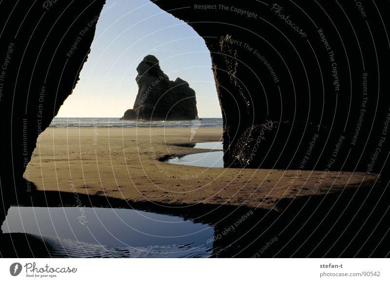 ausblick Neuseeland Nordinsel See Meer Reflexion & Spiegelung schwarz braun Tunnel Höhle dunkel Horizont Stimmung ruhig Torbogen Zeit Gedanke Konstruktion