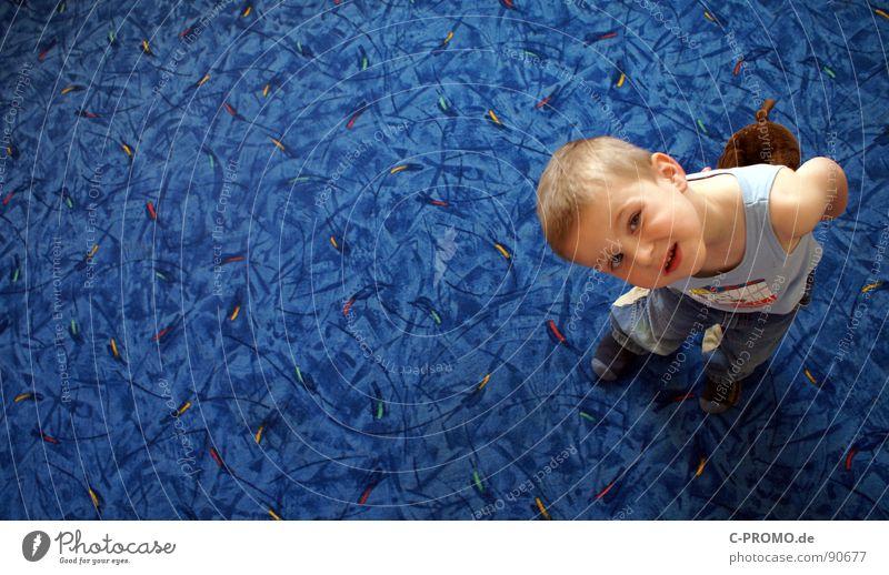 Junge schaut skeptisch nach oben Teppich Kind Kleinkind Freude blau lustig Kindererziehung Gesicht erziehungswissenschaft loben autorität