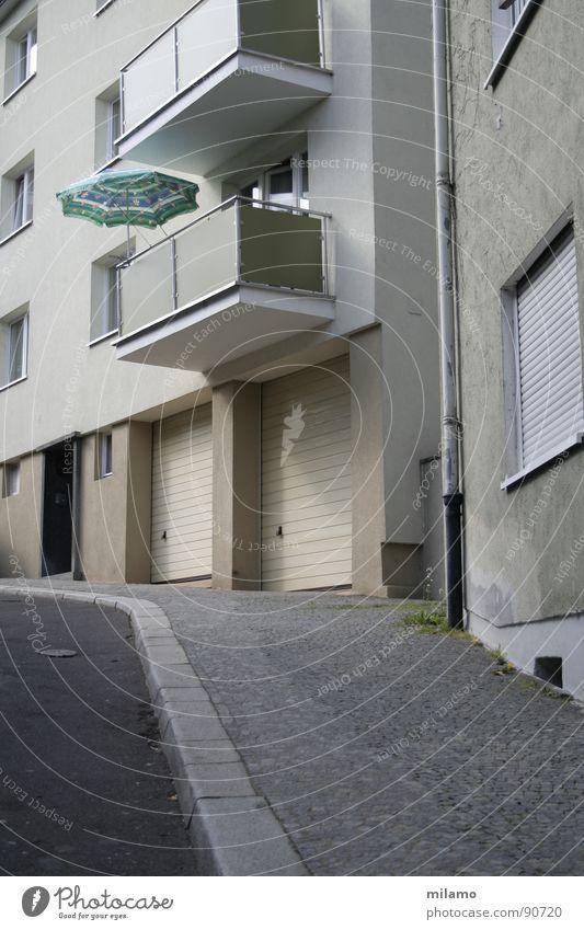 Straßenkomposition Wand Fenster grau Fassade Asphalt Balkon Sonnenschirm Bürgersteig türkis Verkehrswege Garage Bordsteinkante