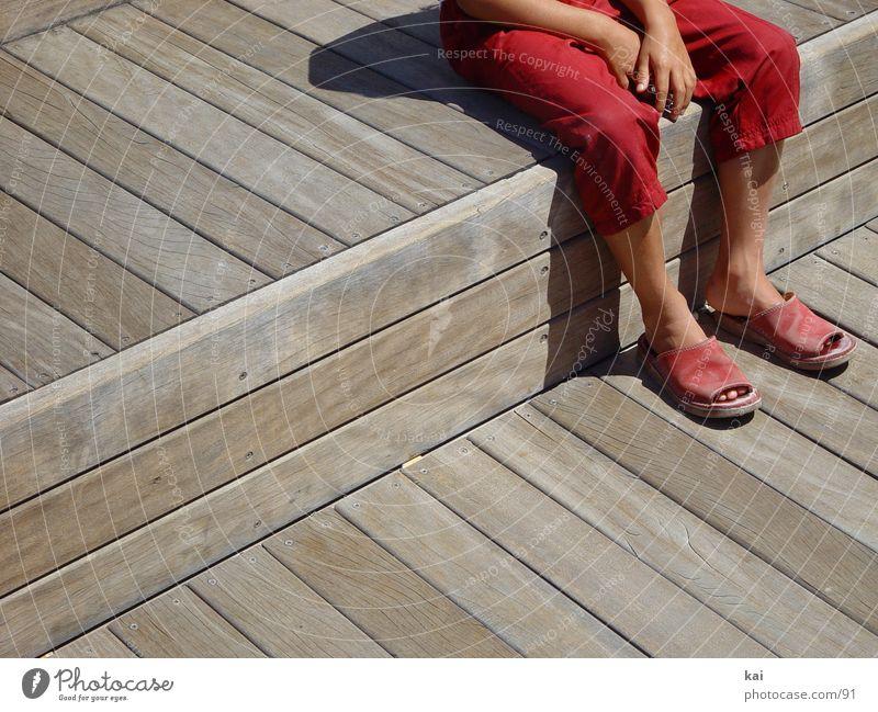 Pause Mädchen Hose rot Hand Fototechnik sitzen Fuß Sandale Bildausschnitt Außenaufnahme warten