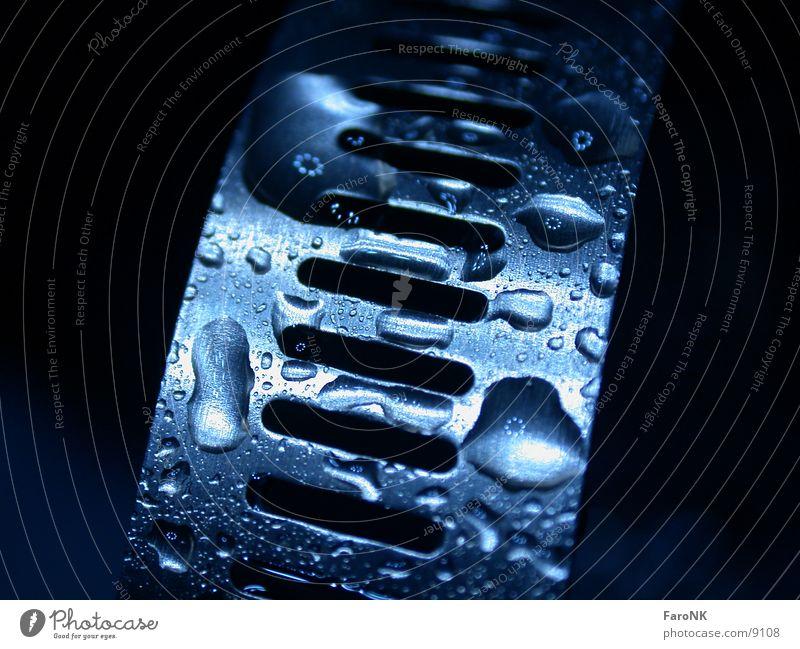Schelle blau Metall glänzend nass Wassertropfen feucht Anschnitt Bildausschnitt schimmern Edelstahl Schelle Vor dunklem Hintergrund