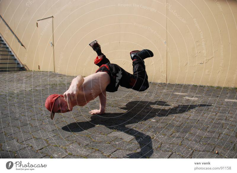 Schwerkraftumgehung Mittelfinger rot Hand Asphalt durchdrehen Jugendliche Breack Breakdancer Tanzen Fick orange Kraft Muskulatur Schatten fly