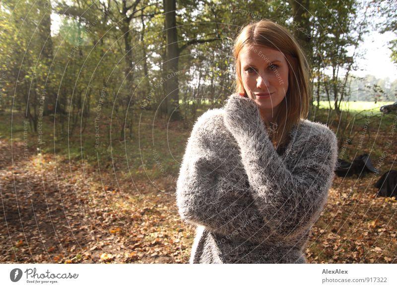 Junge Frau in grauem Pullover steht im Wald auf einer Lichtung Ausflug Jugendliche 18-30 Jahre Erwachsene Natur Landschaft Schönes Wetter Pflanze Baum Sträucher